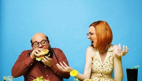 kép leírása: egy fehér, szemüveges kopaszodó férfi egy hamburgerbe harap, mellette egy fehér vörös nő dühös arccal szóra nyitja a száját